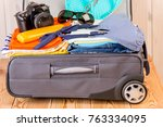 a suitcase stuffed with things... | Shutterstock . vector #763334095