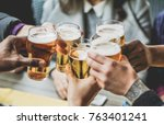 Stock photo group of friends enjoying a beer in brewery pub young people hands cheering at bar restaurant 763401241