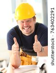 Small photo of Smiling worker in yellow helmet show confirm sign with thumb up at arm portrait.