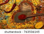 Small photo of Composition of condiment making heart shape. Wood spoons with turmeric, paprika, anise stars, chili pepper and scattered seasoning. Set of spices on wooden background. Cuisine and flavouring concept