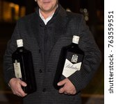 Small photo of Lutsk, Volyn / Ukraine - November 17 2017: Man with two big bottles of scotch whiskey posing at park