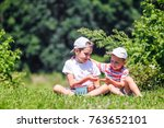 Small photo of children eat raspberries on a farm. boys share berries. copy space for your text