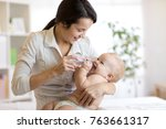 mother giving baby son water... | Shutterstock . vector #763661317