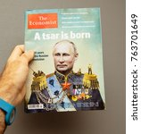 Small photo of STRASBOURG, FRANCE - OCT 28, 2017: POV of man holding The Economist magazine against gray background featuring Vladimir Putin on cover and headline A Tsar is Born