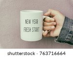 Small photo of Hands Holding a Coffee Mug With Text New Year Fresh Start