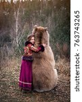 Small photo of A girl in the Russian national dress hugging a real brown big bear. Lte autumn period in the forest