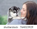 Stock photo young women holds her best friend little pet puppy of husky in her arms love for dogs 764015929
