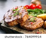grilled beef steaks on wooden... | Shutterstock . vector #764099914