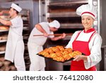 A female baker holding freshly baked croissants in bakery - stock photo