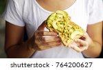 woman hand show eating avocado... | Shutterstock . vector #764200627