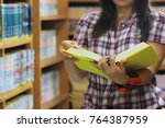 woman reading book in library... | Shutterstock . vector #764387959