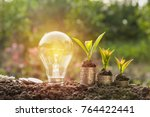 Small photo of Energy saving light bulb and tree growing on stacks of coins on nature background. Saving, accounting and financial concept.