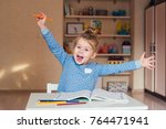 funny girl at the table raised... | Shutterstock . vector #764471941