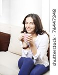 Beautiful young woman drinking her morning coffee - stock photo