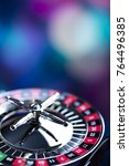 Small photo of Casino theme. High contrast image of casino roulette, poker game, dice game, poker chips on a gaming table, all on colorful bokeh background. Place for typography and logo.