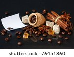 Roasted coffee beans in a clay pot, brown sugar and spices on a shiny black. - stock photo