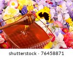 Glass pot with honey with many flowers - stock photo