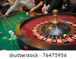 Roulette and piles of chips on a green table - stock photo