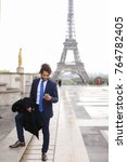 Small photo of Young pressman reading newspaper article near Eiffel Tower and looking at watch. Handsome boy wears suit with blue tie, watch, ring and earring, has dark curly hair and beard. Concept of press public