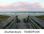 South Carolina nature background. Wooden boardwalk and stairs to the ocean beach over sand dunes in Huntington Beach State Park, Myrtle Beach area, South Carolina, USA. After sunset seascape.