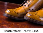 Small photo of Footwear and Shoes Concepts. Pair of Premium Tanned Brogue Derby Boots Made of Calf Leather with Rubber Sole. Shoot Against Dark Background.Horizontal Image Orientation