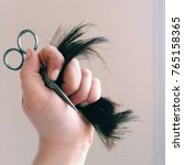 Small photo of Handful of hair and scissors after cutting bangs