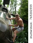 Small photo of Sportsman with muscle body on heli aircraft. Man climb on helicopter in forest. Goal, achievement, success. Travelling, discovery, adventure. Ambition, dream, priority concept.