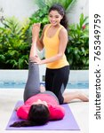 Small photo of Young woman helping her friend to raise leg in correct position in abdominal workout