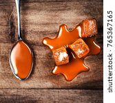 Small photo of Homemade salted caramel pieces on wooden background. Golden Butterscotch toffee candy caramels with copyspace