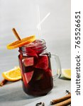 Small photo of Red Sangria with Orange and Cinnamon Stick on Gray Background