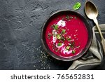 Small photo of Beetroot creamy soup in a dark clay bowl over black slate,stone or concrete background.Top view with copy space.