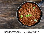 Small photo of bolognese sauce - hot juicy ground beef stewed with tomato sauce, spices, basil, finely chopped vegetables and celery in skillet on wooden table, authentic recipe, view from above