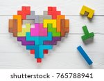 Small photo of Heart made of colorful wooden shapes, top view, flat lay. Health background concept. Logical tasks. Conundrum, find the missing piece of the proposed.
