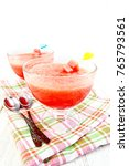 Small photo of Jelly airy watermelon in two glass bowls, a spoon on a towel on the background of a wooden board
