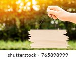 Small photo of Woman hand holding show a label wood board on sunlight in the public park, Copy space for advertising and announce concept.