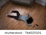 Small photo of murder, kill and people concept - unconscious or dead woman body and smartphone lying on floor at crime scene (staged photo)