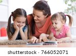pretty mother reading a book to ... | Shutterstock . vector #766052071
