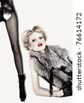 Blond fashion model in fur and red lipstick  , black fishnet stockings and high-heels - stock photo