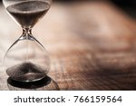 Small photo of Hourglass as time passing concept for business deadline, urgency and running out of time. Sandglass, egg timer on wooden floor showing the last second or last minute or time out. With copy space.