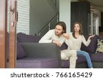 Small photo of Frustrated angry man sitting on couch turned his back ignoring wife blaming shouting at him, young married couple having quarrel at home, unhappy husband and wife arguing, problems in relationships