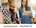 shop owner checking stocks with ... | Shutterstock . vector #766346731