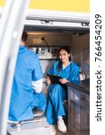 Small photo of smiling Asian paramedic holding clipboard and sitting in ambulance