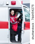 Small photo of smiling paramedic sitting in ambulance and holding clipboard