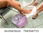 female feet in a vibrating foot ... | Shutterstock . vector #766566715