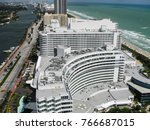 Small photo of Miami, Florida USA - October 6, 2010: View of the luxury resort hotels Fountainebleau and Eden Roc looking north along Miami Beach, the Atlantic Ocean beach on the right, Intercoastal Waterway on left