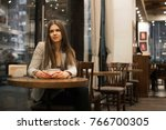 the girl sits in a cafe and... | Shutterstock . vector #766700305