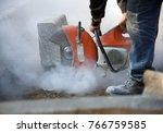 A worker cuts concrete curb...