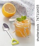 Small photo of Glass jar full of lemon curd with cute spoon and meant leaf upon rustic table. Selective focus.