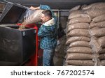 Small photo of the man loads the pellets in the solid fuel boiler, working with biofuels, economical heating