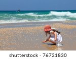 Little Girl Collects Shells On...